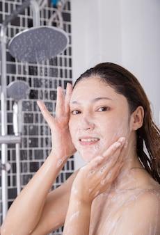 Waschendes gesicht der frau in der schäumenden dusche