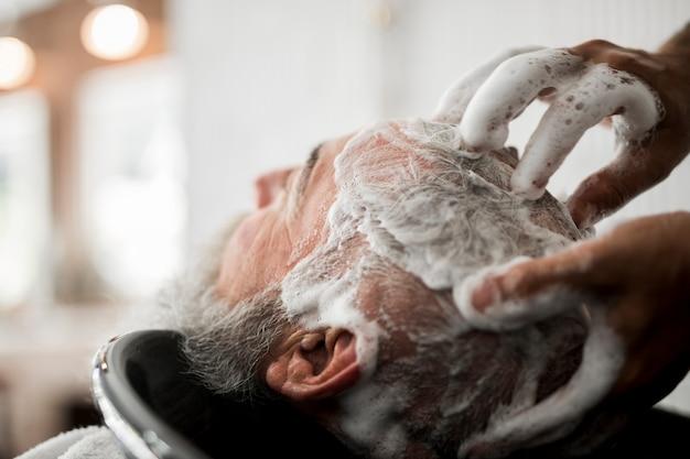 Waschendes haar des älteren mannes im friseursalon