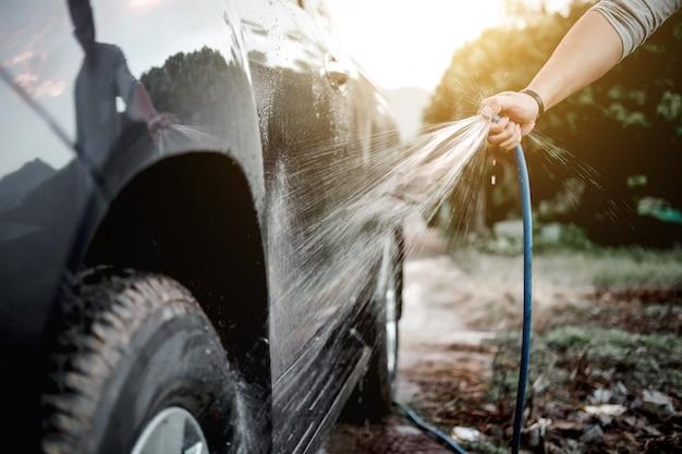 Waschendes und säuberndes auto des mannes mit dem sprühen unter druck wasser