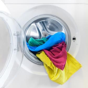 Waschmaschine mit bunten kleidern nahaufnahme geladen.