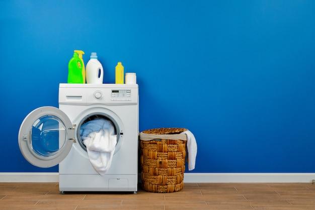 Waschmaschine mit wäsche an der blauen wand