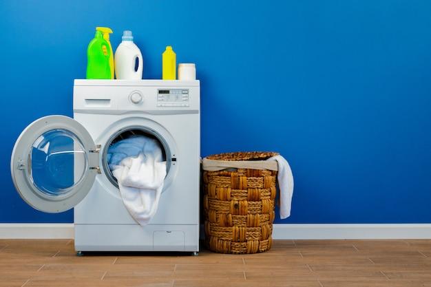 Waschmaschine mit wäsche auf blauem wandhintergrund