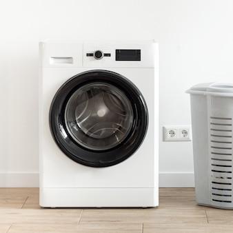 Waschmaschine mit wäschekorb in der waschküche