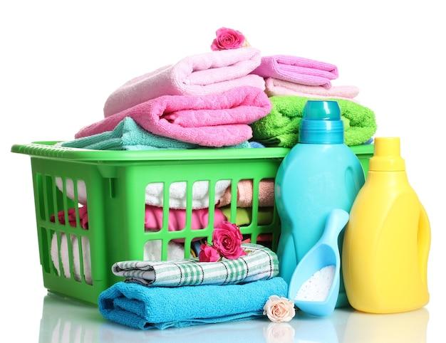 Waschmittel und handtücher im grünen plastikkorb isoliert auf weiß