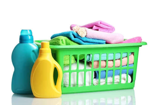 Waschmittel und handtücher in grünem plastikkorb auf weiß Premium Fotos