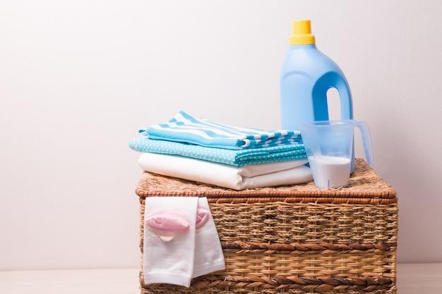 Waschmittel, waschgel und wäsche auf einem weidenkorb