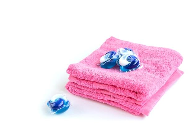 Waschmittelkapselhülsen und rosa handtuch isoliert auf weiß.