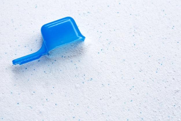 Waschpulver mit messlöffel zum waschen der kleidung. wäschereikonzept.