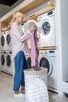 Waschzeit. blonde frau im gestreiften hemd, das kleidung aus korb nimmt