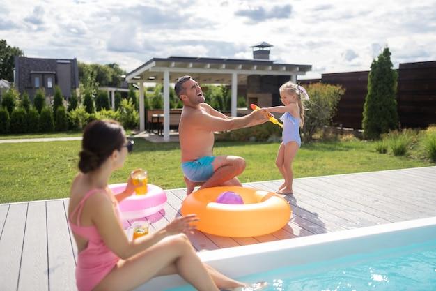 Wasser auf papa. lustige tochter, die papa mit wasser spritzt, während sie spaß mit den eltern in der nähe des pools hat