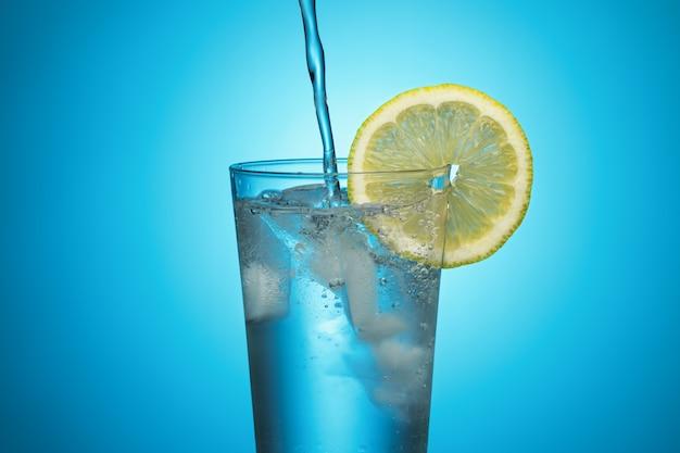 Wasser aus einer flasche wird in ein glas mit eis und zitrone auf blauem grund gegossen.
