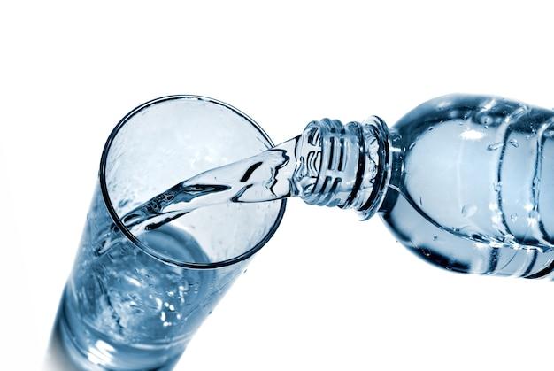 Wasser, das in glas aus der flasche gießt, isoliert auf weiß