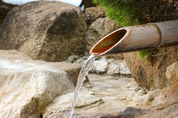Wasser der heißen quelle des japanischen bambusrohres, das in onsen pool fließt.