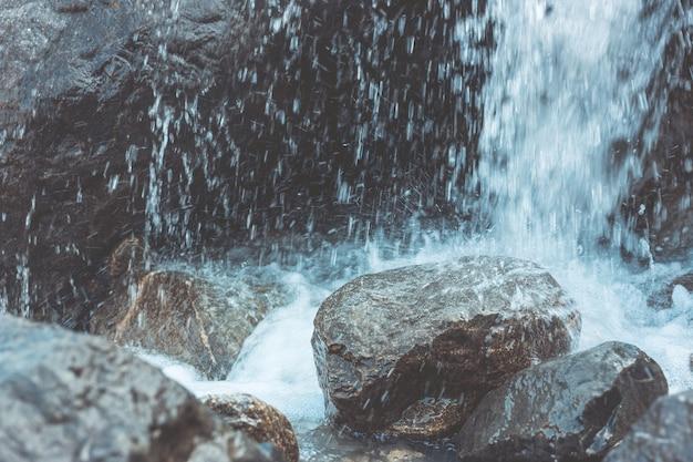 Wasser fällt auf steine und felsbrocken. spritzer, regen, feuchtigkeit. eng gefilmt.