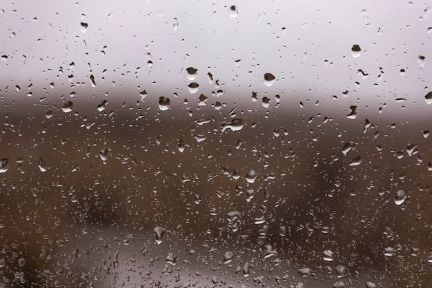 Wasser fällt nach dem regen in ein dunkles fensterglas