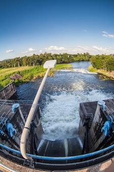 Wasser fließt aus den offenen schleusentoren des damms.