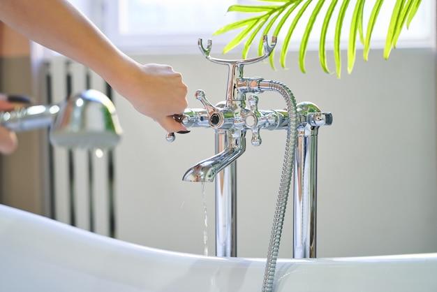 Wasser fließt aus der dusche auf die hände des mädchens.
