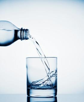 Wasser fließt aus der flasche in ein breites glas