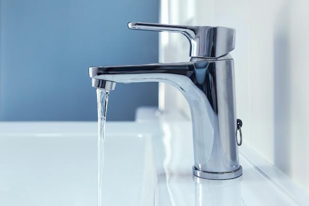 Wasser fließt aus einem glänzenden chromhahn in die spüle.