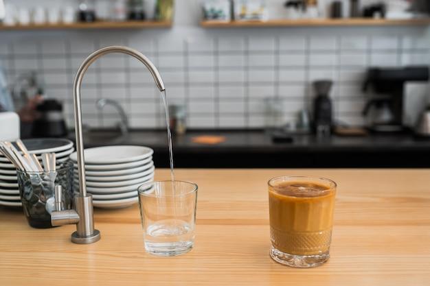 Wasser fließt aus einem wasserhahn in ein glas