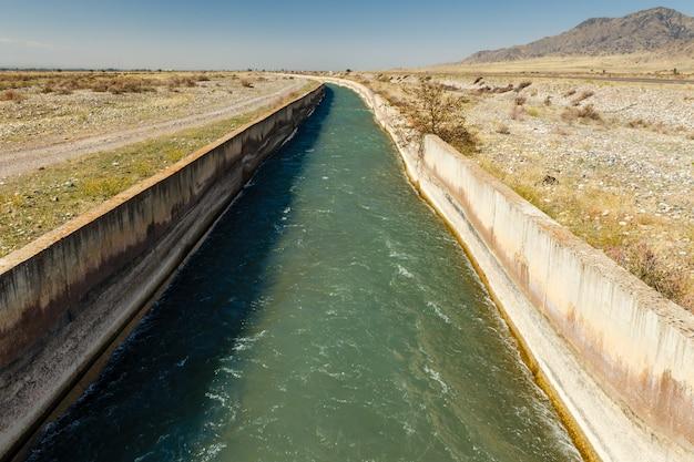 Wasser fließt in einem bewässerungskanal in kirgisistan