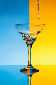 Wasser gießt in glas über blaue und gelbe wand