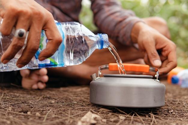 Wasser in einen wasserkocher gießen. bali