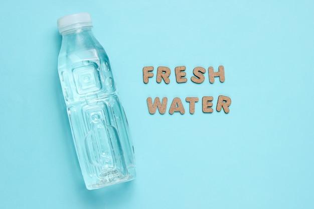 Wasser in flaschen auf blauer oberfläche mit den worten süßwasser.