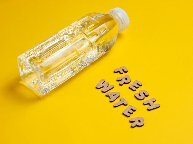 Wasser in flaschen auf gelber oberfläche mit den worten süßwasser.
