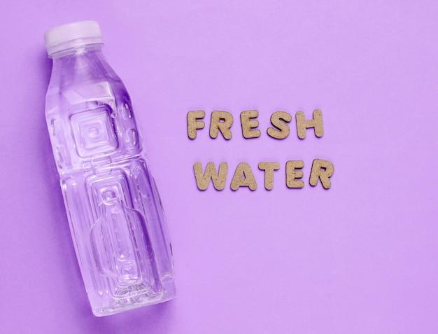 Wasser in flaschen auf lila mit den worten frisches wasser.