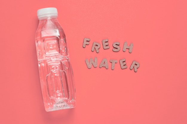 Wasser in flaschen auf rosa mit den worten süßwasser.