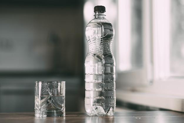 Wasser in flaschen und ein glas auf dem tisch zu hause in der küche