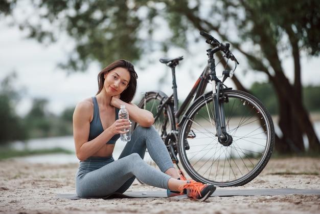 Wasser ist sehr wichtig. weibliche radfahrerin mit guter körperform, die tagsüber nahe ihrem fahrrad am strand sitzt