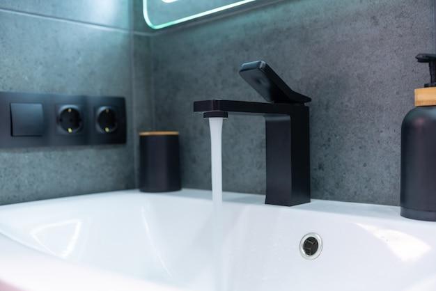 Wasser läuft aus einer mischbatterie in ein keramisches handwaschbecken