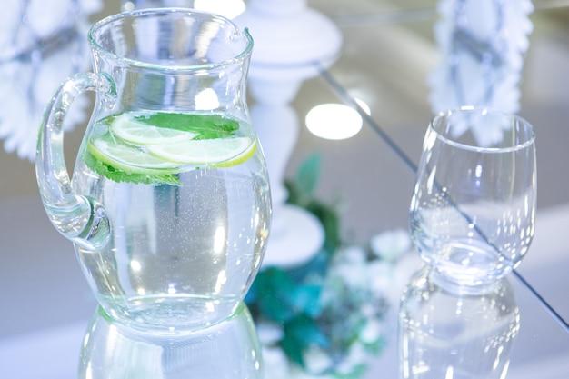 Wasser mit frischer zitrone und minze in einem krug auf einem glastisch
