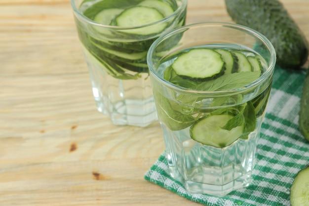 Wasser mit gurke. erfrischendes diätwasser mit gurke und minze in einem becherglas auf einem holztisch. detox-getränkekonzept.