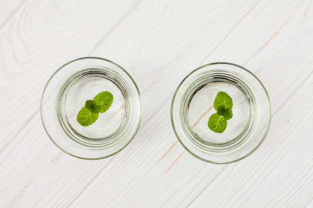 Wasser mit minze in den gläsern auf weißer tabelle