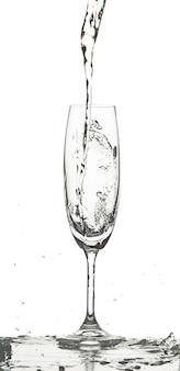 Wasser spritzt in glas auf weißem hintergrund