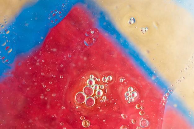 Wasser sprudelt über dem dreieckigen gemalten bunten hintergrund