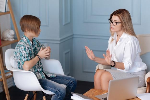 Wasser trinken. kluge weibliche psychologin, die weißes hemd und rock trägt, die im sofa sitzen hände in der luft halten