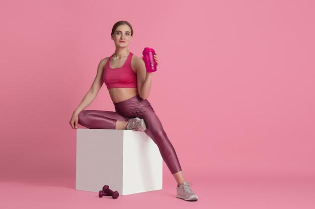 Wasser trinken. schöne junge sportlerin üben, einfarbiges rosa porträt. sportliches fit-modelltraining mit sprungbox. bodybuilding, gesunder lebensstil, schönheits- und aktionskonzept.
