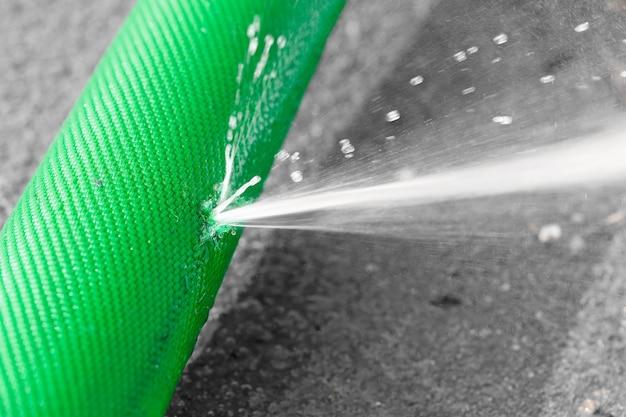 Wasser tritt aus einem loch in einem schlauch aus