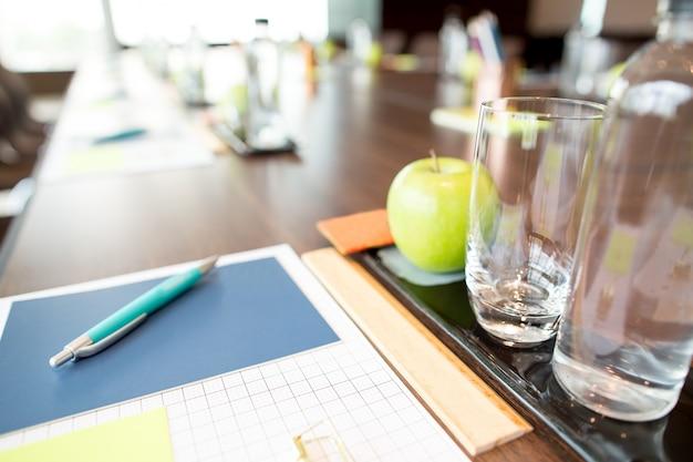 Wasser- und schreibgeräte auf konferenztisch