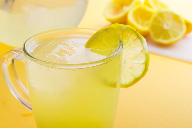 Wasser und zitrone im gelben hintergrund