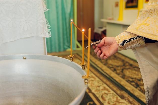 Wasser wird in die schrift gegossen, um das baby in der kirche zu baden, religiöse traditionen.