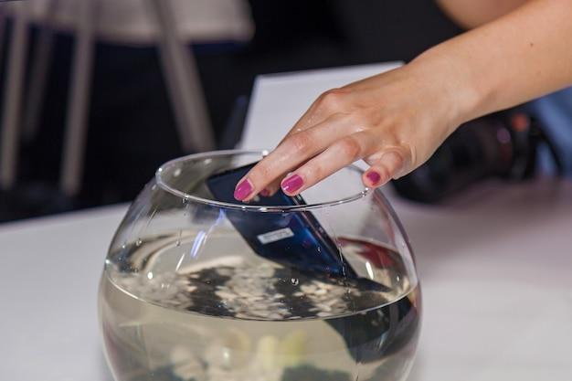 Wasserdichtes telefon unter wasser in einem runden aquarium, das mädchen zieht das telefon aus dem aquarium