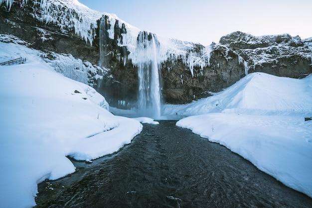 Wasserfälle fließen zwischen schnee