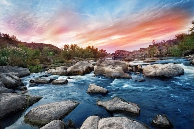 Wasserfall am gebirgsfluss mit grauen steinen