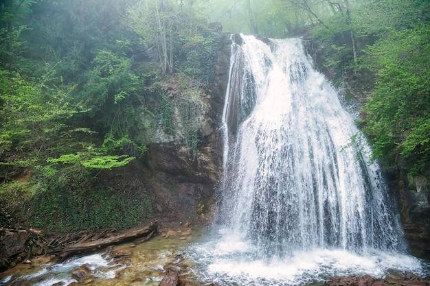 Wasserfall auf dem fluss bedeckte grüne blätter im tiefen wald. wasserfall in angenehmer umgebung. werbehintergründe für die website oder großauflösende tapeten. konzept von natur, tourismus und abenteuer
