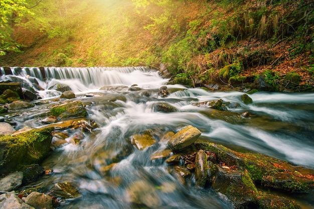 Wasserfall auf einem gebirgsfluss im herbstwald unter strahlender sonne